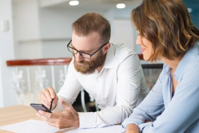 Marketing group working on new business plan. Serious office employee wearing glasses, using calculator, his female colleague following him. Teamwork concept